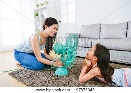 sweet little children girl lying down on living room floor and elegant mother using electric fan let her enjoying cool wind at summer day.