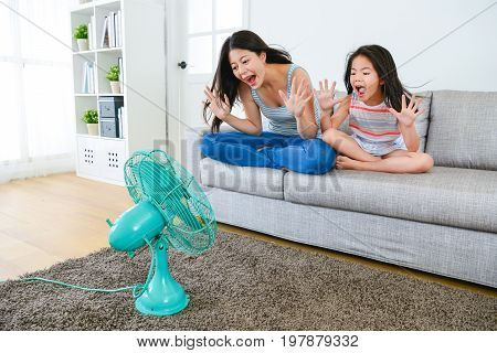 Mother With Little Girl Sitting On Couch Sofa