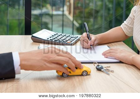 Woman signing car loan agreement contract with car key and calculator on wooden desk