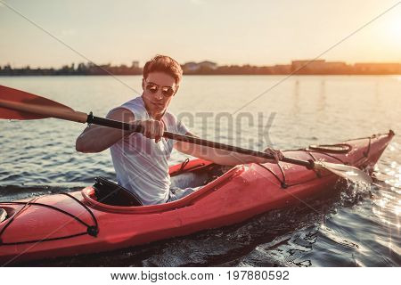 Man Kayaking On Sunset