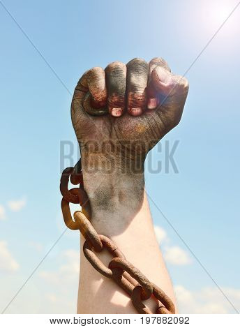 The man's hand is encased in an iron rusty chain against the sky