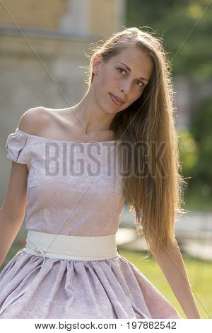 Portrait of a beautiful woman with long hair in a pink dress. Stock photo
