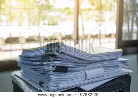 Stack of papers files on work desk in office business report paper or piles of unfinished documents achives with clips on offices desk Business concept
