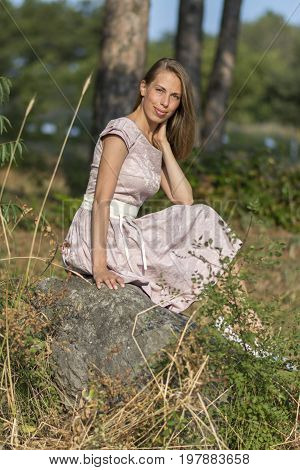 Beautiful girl in the field. Women sits on a rock, enjoying the outdoors and the sun. Country holiday, holiday, forest - The concept of country vacation. Article about the weekend in the country. Stock photo