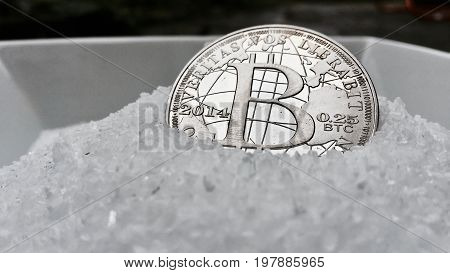 Digital currency physical metal coin on the white cristal background. Virtual cash concept.