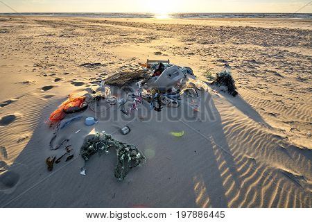 Trash at the beach covered with sand during sunset at Texel Netherlands. Ocean and horizon in the background.