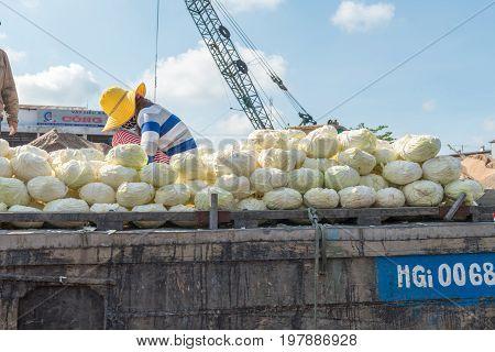 MEKONG DELTA, VIETNAM - April 25, 2014 - Cabbage vendor at Asian floating market on Mekong river in Vietnam