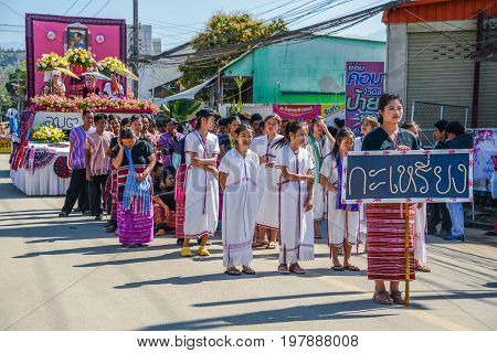 CHIANGMAI THAILAND - JANUARY 25 2015: Hill Tribe people with traditional costume holding board of Karen nationality name in parade of 22nd Traditional Skirt Fabric and The Indigenous Product and Culture Festival in Mae Chaem Chiangmai Thailand