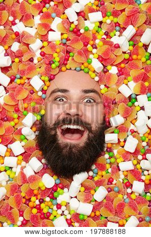 Young bearded man looking extremely excited while lying in candies and sweets.