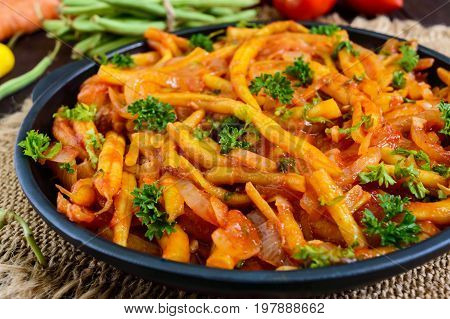 Spicy green beans stewed with onions carrots in tomato sauce. Serve on a cast-iron frying pan
