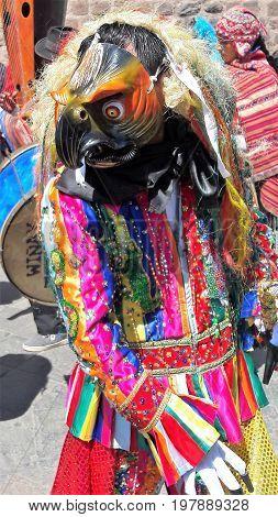 Reveler wearing eye-catching mask in street parade in Cuzco, Peru