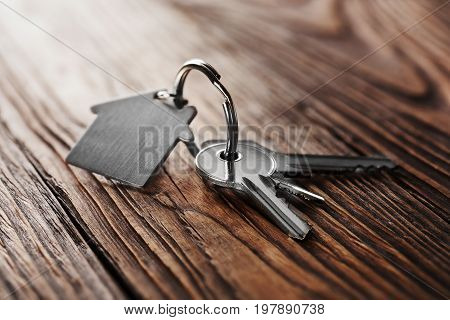 House Key On  House Shaped Keychain  On Wooden Floorboards