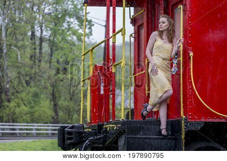 A redhead model posing on a train in the rain