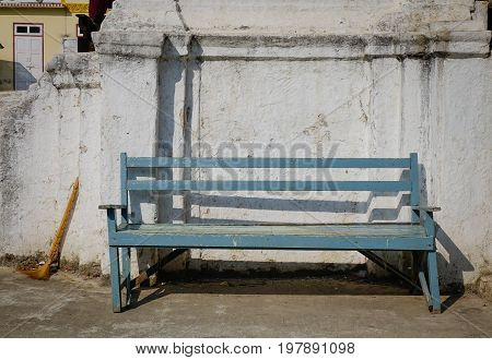 A Vintage Blue Bench With Old Wall At Sunny Day