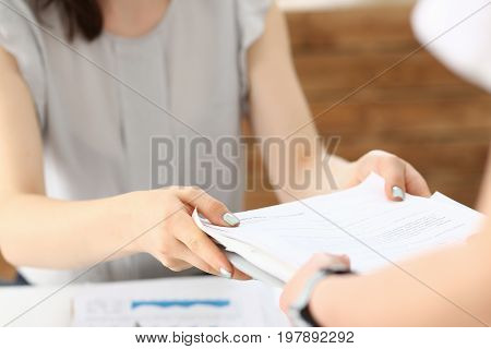 Female employee show pack of documents to busy male manager or boss give extra work to executor. White collar portrait contract approval headache and depression irs lot of new problems concept
