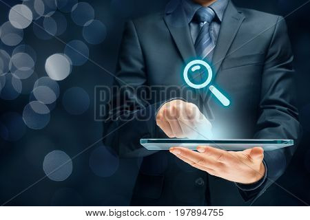 Search, find and SEO internet concepts. Businessman hold futuristic tablet with head-up display and symbol of loupe.