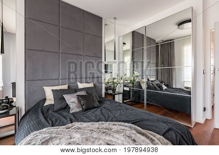 Luxurious bedroom with mirrored wardrobe double bed and upholstered wall