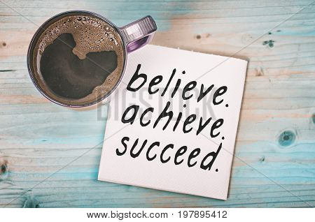 Believe achieve succeed. Motivational quote handwritten on napkin with a coffee cup.