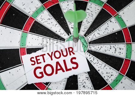 Set Your Goals on notepaper with dart arrow and dart board. Business concept.