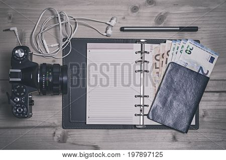 Travel trip vacation tourism mockup - close up of camera passport with money earphones note pad and pen on wooden table. Empty space for your text or information.
