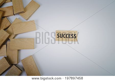 Success word written on wood block on white background. Leadership and guidance in business concept.