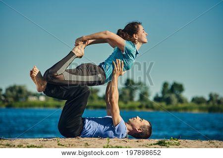 Young healthy couple balancing and doing acro yoga