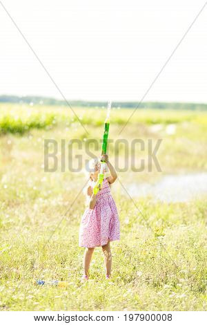 Girl poured from a water pistol. Children play with water pistols.