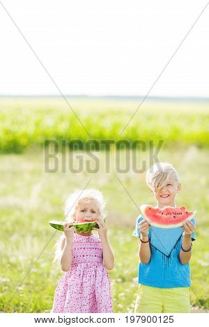 A boy and a girl are holding watermelon slices. A brother and sister with blond hair eat a watermelon. Brother and sister having fun