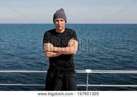 Confident handsome man standing with arms crossed at the ocean leaning on handrail and looking at camera.