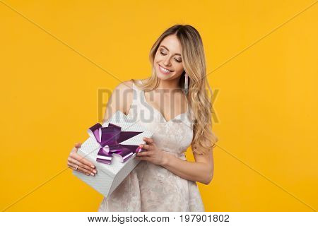 Young woman in white dress looking happy and holding giftbox on orange background.