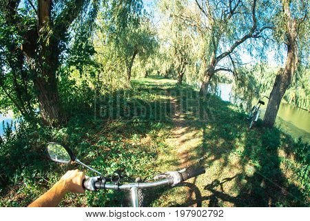 The bicycle handlebars on which the biker's hand is near the pond