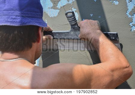 Fifty Years Old Manual Worker With Wall Plastering Tools Renovating House. Plasterer Renovating Wall