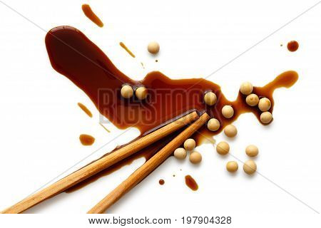 Spilled soya sauce and soya beans on white from above with chopsticks.