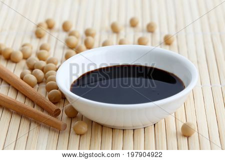 Soya Sauce In White Bowl On Bamboo Mat With Chopsticks And Spilled Soya Beans.