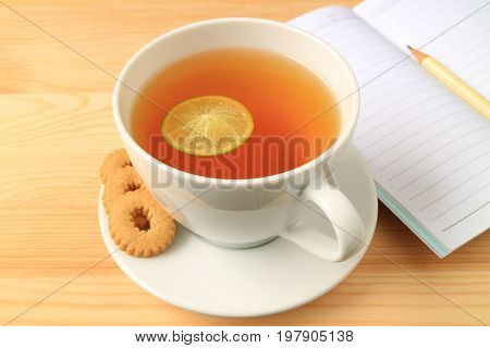Cup of Hot Lemon Tea with Cookies and Lined Note Papers on Wooden Table