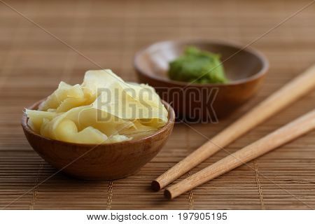 Pickled Ginger Slices In Wooden Bowl On Bamboo Mat Next To Chopsticks And Wasabi Paste In A Bowl.