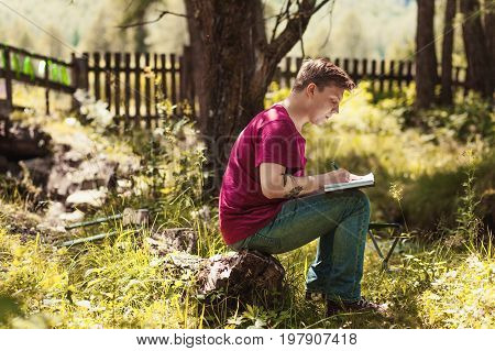 Young Man reading book and writing notes on background Summer vacations and Lifestyle concept.