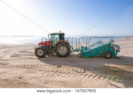 red tractor with trailer cleaner cleaning sand in Els Terrers Beach Benicassim Castellon Valencia Spain Europe. Mediterranean Sea