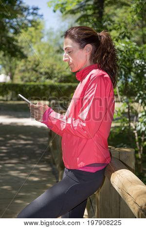 sporty adult woman with pink sweater watching mobile smartphone leaning in wooden railing of footbridge in park of Retiro in Madrid Spain. Vertical shot