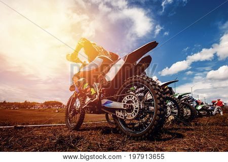 Racer on a motorcycle participates in motocross prepare for the start against a team of rivals. Concept active extreme rest. ray of light