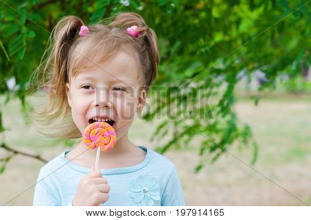 Portrait Of A Beautiful Girl With A Lollipop, Free Space. Happy Child With A Lollipop.