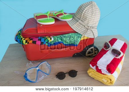 Anticipation of voyage. Women's clothes and accessories in red suitcase things prepared for travel