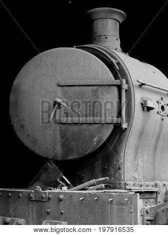 old rusty steam locomotive with door open and chimney in front view on black background