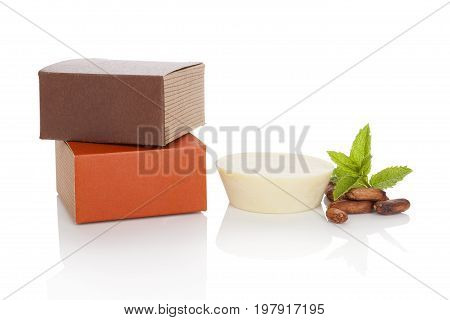 Natural cosmetics. Cocoa and mint massage soap with cocoa seeds and mint leaves isolated on white background.