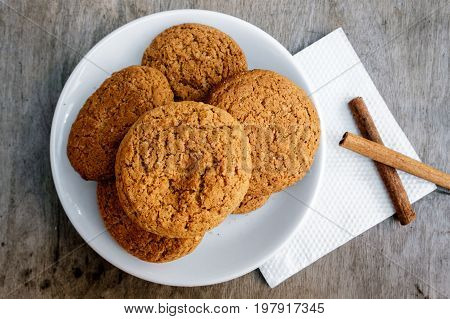 Oatmeal cookies with raisin are on a wooden table. Cookies are made in house conditions.