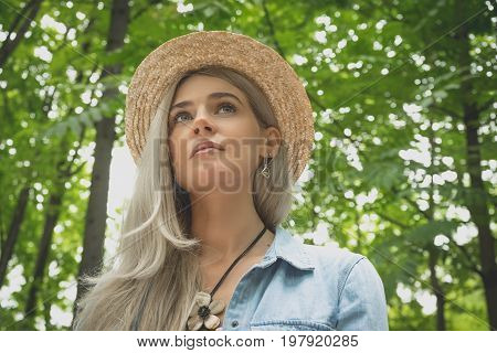 A young woman in a straw hat mysteriously looks up at the sky, expressive close-up eyes. The concept of freedom, freedom, lifestyle, balance, connection with nature and the green world