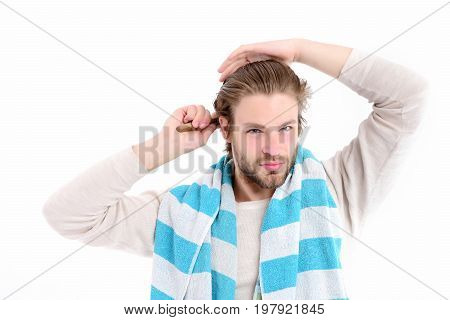 Man with concentrated face and beard brushes his wet hair. Idea of morning routine. Morning time routine concept. Macho with striped blue and white towel on his neck isolated on white background poster