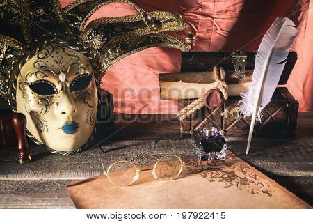 Theater concept. Vintage still life with quill and scroll near mask old chest and glasses on red background.
