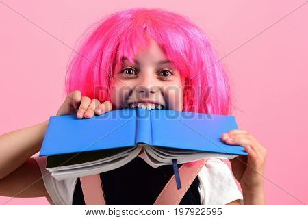 School Girl Bites Big Blue Book Isolated On Pink Background.