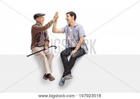 Senior and a young guy sitting on a panel and high-fiving each other isolated on white background